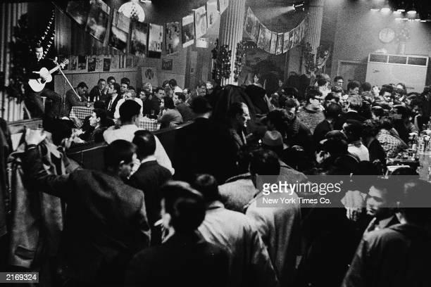 A folk musician plays acoustic guitar for a crowded audience inside Gerde's Folk City nightclub near West 4th Street and Broadway Greenwich Village...
