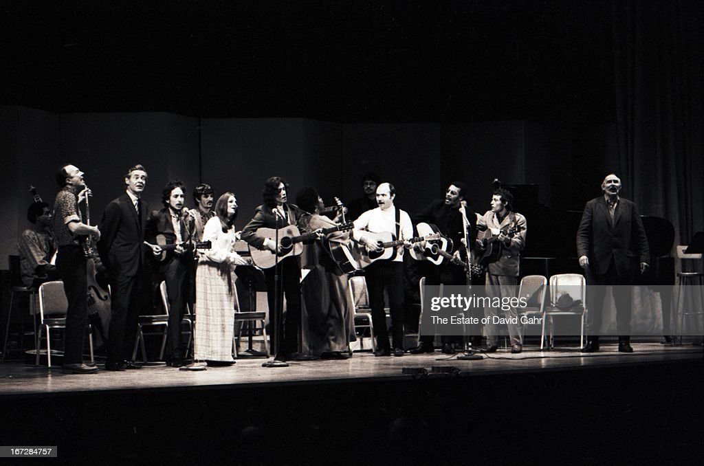 Folk musicians including (l-r) bassist and composer Bill Lee, folk singer Pete Seeger, actor Robert Ryan, singer songwriter Bob Dylan, musician Rick Danko of rock group The Band, folk singer Judy Collins, singer songwriter Arlo Guthrie, folk singer Odetta, guitarist Robbie Robertson of rock group The Band, folk singer and songwriter Tom Paxton, folk musician Richie Havens, folk singer Jack Elliott, and actor Will Geer perform at the Woody Guthrie Memorial Concert, a concert produced by folk music impresario Harold Leventhal, at Carnegie Hall on January 20th, 1968 in New York City, New York.