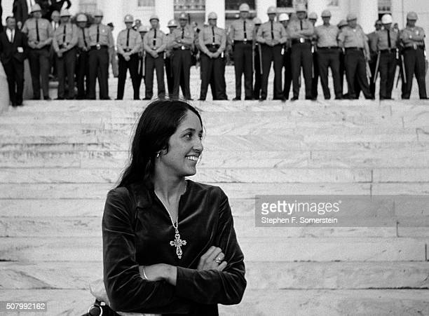 Folk singer and activist Joan Baez stands in front of state police on State House steps at the end of the Selma To Montgomery Civil Rights March on...