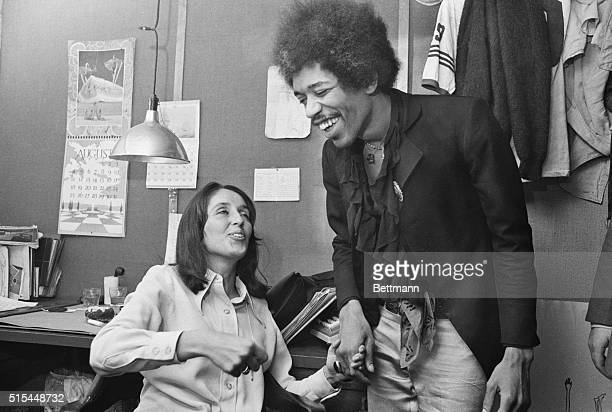 Folk singer Joan Baez and rock singer Jimi Hendrix chat between acts at a Biafran Relief Benefit show at a place in Manhattan called Steve Paul's...