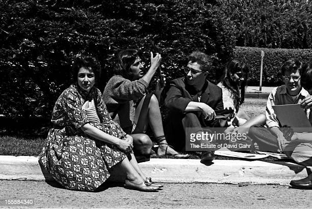 Folk singer Joan Baez and Vanguard Records founder Maynard Solomon socialize with friends and folk fans in June 1960 at the Newport Folk Festival in...