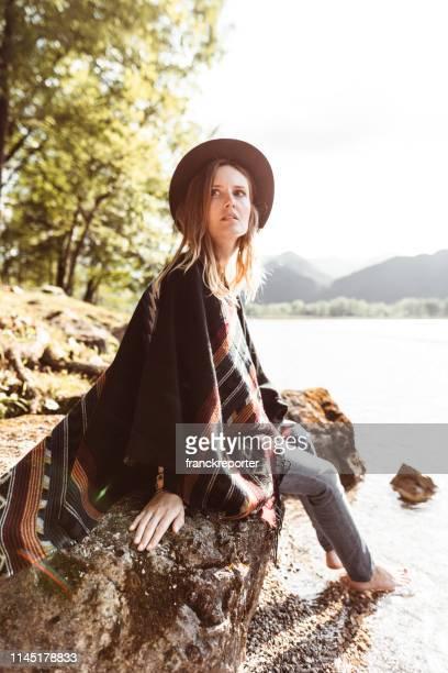 folk woman with a poncho sitting on a stone