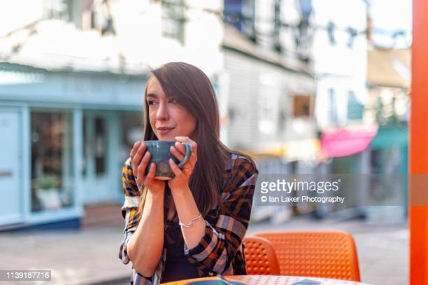 folkestone, kent, england. 24 march 2019. young woman drinking coffee outside coffee shop. - 30 34 years stock pictures, royalty-free photos & images