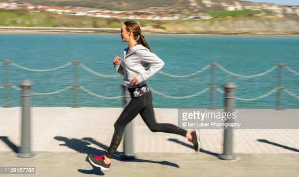 folkestone, kent, england. 24 march 2019. young woman running. side view. - striding stock pictures, royalty-free photos & images