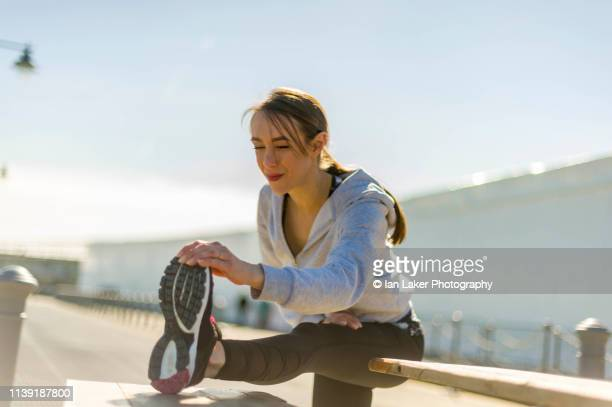 folkestone, kent, england. 24 march 2019. young woman stretching calf muscle. - stretching stock pictures, royalty-free photos & images