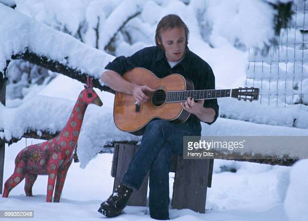 Folkrock singer Stephen Stills plays a guitar in a snow covered meadow in Colorado Stills became wellknown in Buffalo Springfield then moved on to...