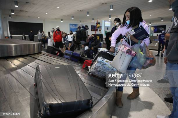 Folks wait to pick up their bags after their arrival to the Oakland International Airport on Tuesday, December 22 in Oakland, Calif. Many people...