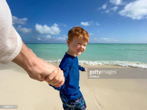 follow me concept - redhead boy holding his mother's hand on tropical beach in the caribbean. - following stock pictures, royalty-free photos & images
