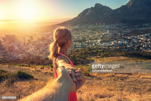 follow me concept- sportive girl leading man - south africa stock pictures, royalty-free photos & images