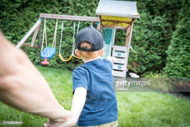 follow me concept - toddler and mother running to the playground - following stock pictures, royalty-free photos & images