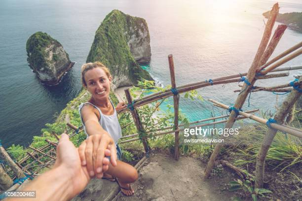 folgen sie mir konzept frau führenden freund am idyllischen strand in unberührten klares wasser in den inseln von thailand. die leute reisen luxus-ferien-destinationen-konzept - following stock-fotos und bilder
