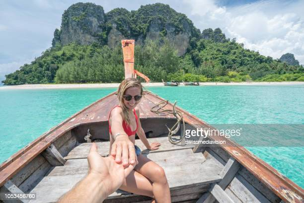 follow me concept woman leading boyfriend on longtail thai boat in pristine clear water in the islands of thailand. people travel destinations fun concept - following stock pictures, royalty-free photos & images