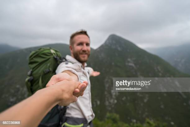 Follow me concept- Young man leading girlfriend in mountain sceneryFollow me