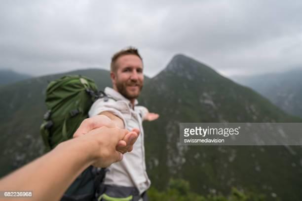 Följ mig koncept-ung man leder flickvän i berg sceneryFollow mig