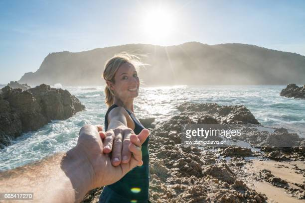 follow me concept- young woman leading boyfriend at the edge of the sea - following stock pictures, royalty-free photos & images
