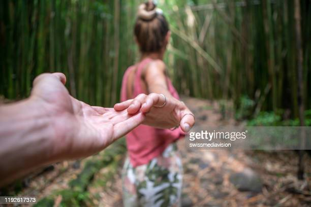 follow me concept, young woman leading boyfriend to bamboo forest - following stock pictures, royalty-free photos & images