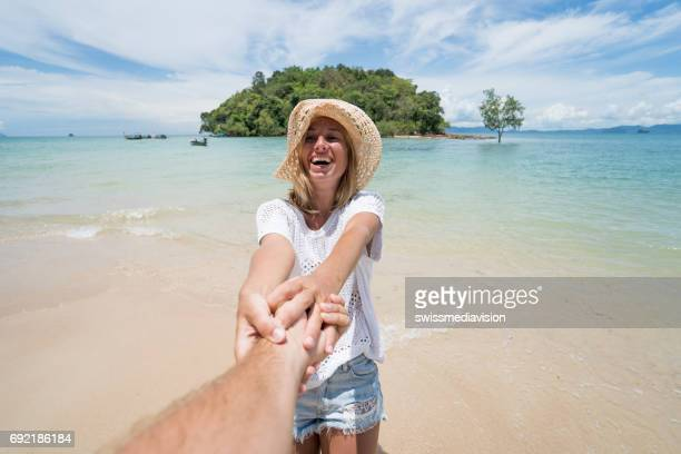 Follow me concept- Young woman leading man to tropical beach
