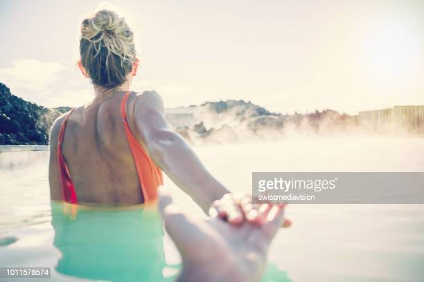 follow me pov - couple in love having fun. boyfriend following girlfriend holding hands in iceland outdoors in nature laughing and smiling enjoying geothermal spa in hot springs blue lagoon thermal baths. - honeymoon stock photos and pictures