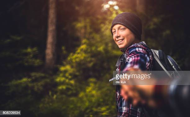 Follow me. Happy boy showing the way during hiking activities