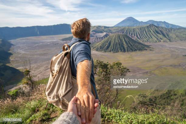 follow me to concept, boyfriend leading person to volcanic landscape in bromo, indonesia. people travel concept - following stock pictures, royalty-free photos & images