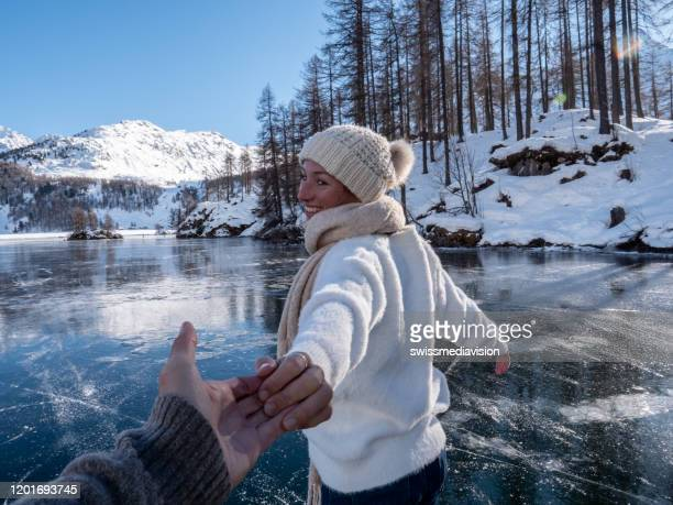 follow me to concept; happy young woman leading boyfriend to frozen lake at sunset - following stock pictures, royalty-free photos & images