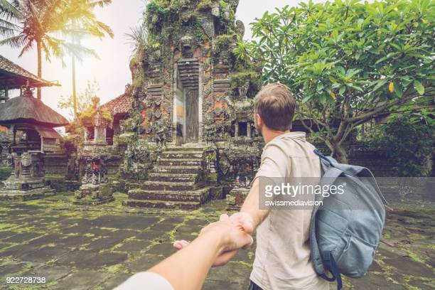 follow me to concept, man leading girlfriend to ancient temple in bali - following stock pictures, royalty-free photos & images
