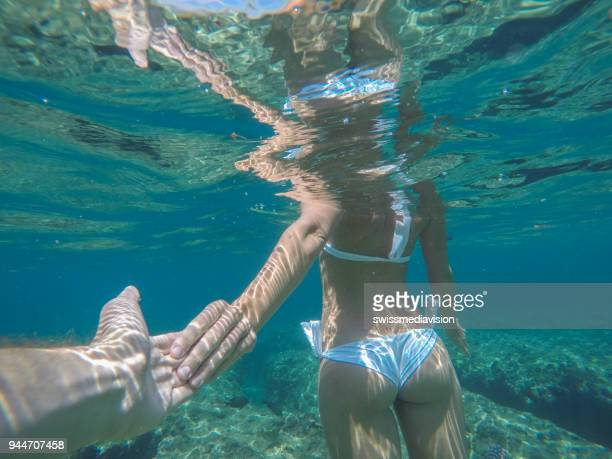 Follow me to concept, underwater shot of young woman leading boyfriend to the sea
