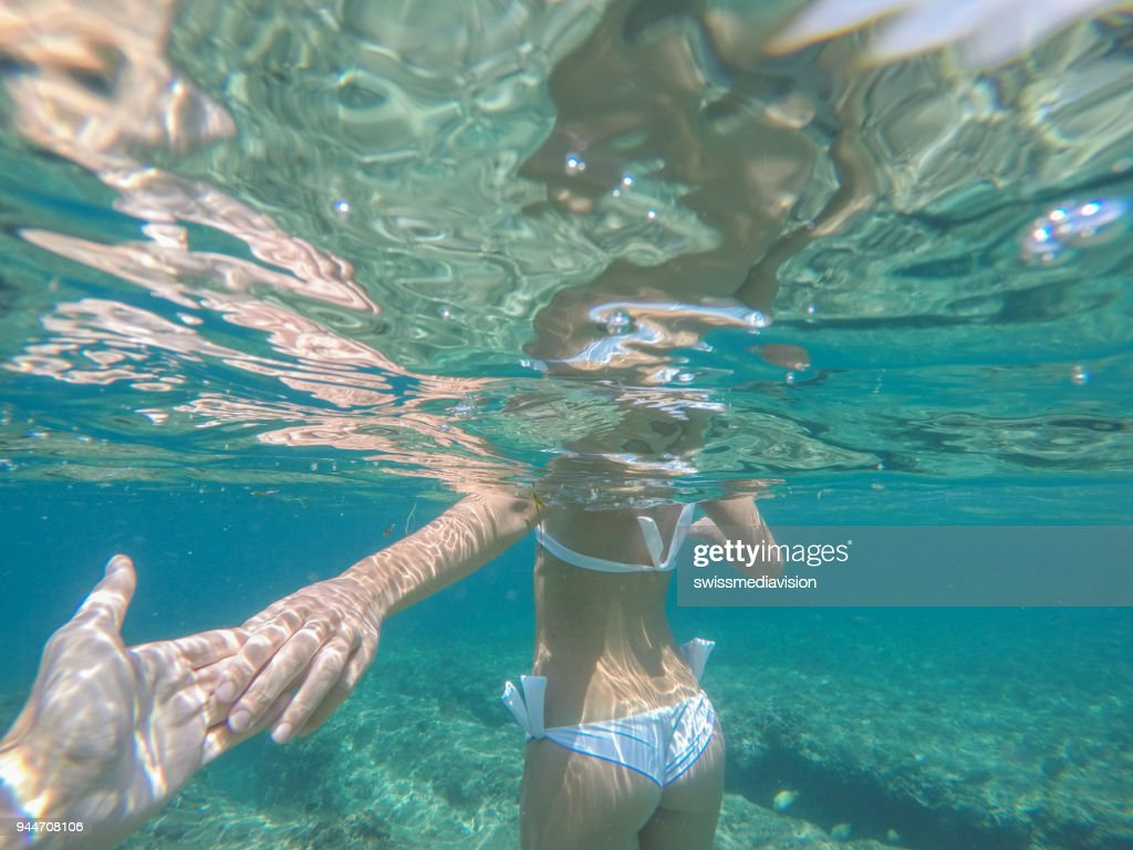 Follow Me To Concept Underwater Shot Of Young Woman Leading