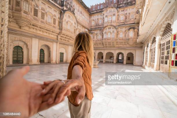 Follow me to concept; woman leading boyfriend holding hands inside the fort at sunset in India