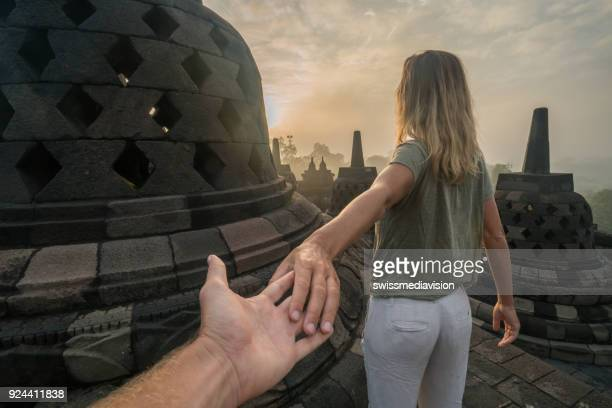 Follow me to concept, woman leading boyfriend to Borobudur temple at sunrise, Indonesia
