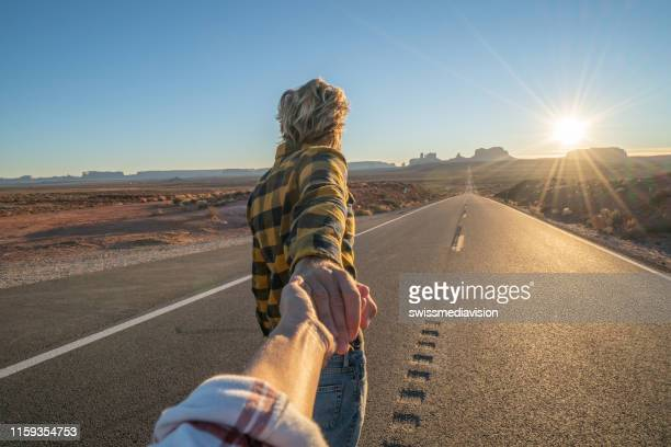 follow me to concept; young man leading boyfriend to long highway road at sunset enjoying travel in the usa - following stock pictures, royalty-free photos & images