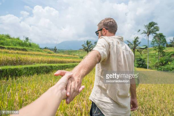 follow me to concept, young man leading girlfriend to rice terraces in bali- indonesia - following stock pictures, royalty-free photos & images