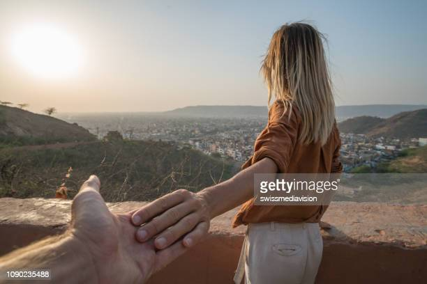 follow me to concept, young woman holding hand of boyfriend leading him to terrace to watch sunset over the city - following stock pictures, royalty-free photos & images