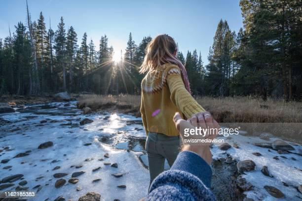 seguimi al concetto, giovane donna che porta il fidanzato al fiume ghiacciato al tramonto, usa - fare da guida foto e immagini stock
