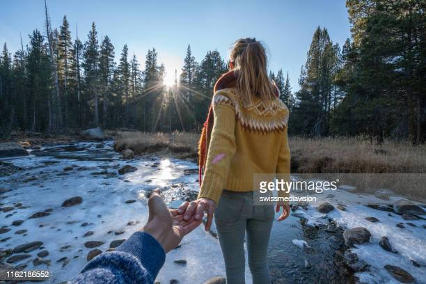 follow me to concept, young woman leading boyfriend to frozen river at sunset, usa - following stock pictures, royalty-free photos & images