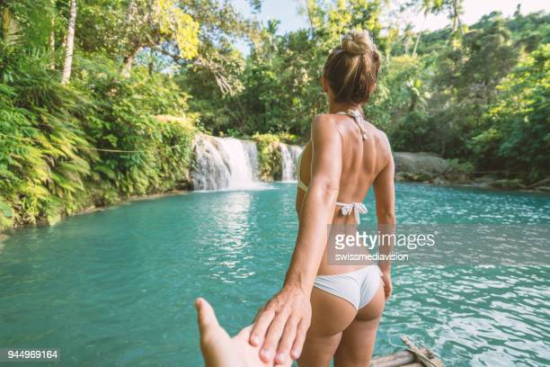 follow me to concept young woman leading boyfriend to idyllic waterfall - following moving activity stock pictures, royalty-free photos & images