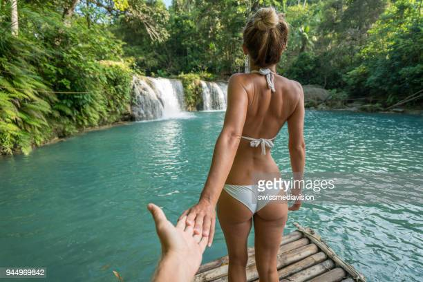 follow me to concept young woman leading boyfriend to idyllic waterfall - following stock pictures, royalty-free photos & images