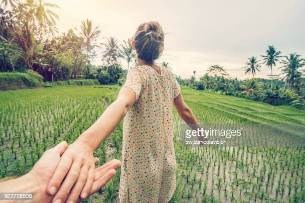 follow me to concept, young woman leading boyfriend to rice terrace in ubud, bali- indonesia - following stock pictures, royalty-free photos & images