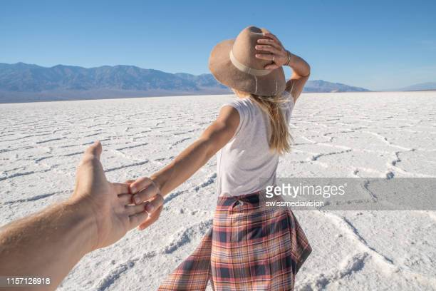 follow me to concept; young woman leading boyfriend to salt flats in the desert - following stock pictures, royalty-free photos & images