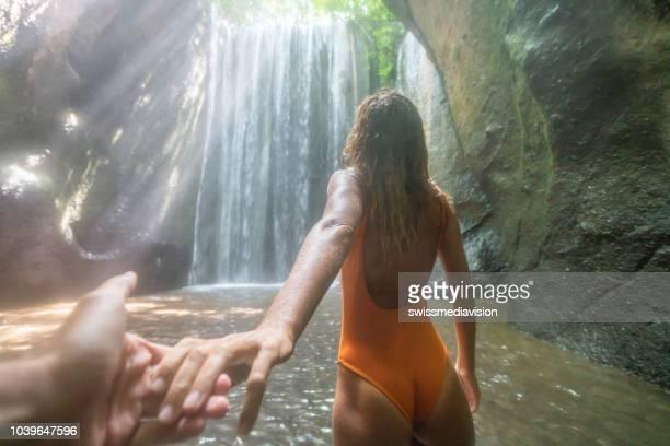 folgen sie mir zu führenden freund konzept-junge frau in den tropischen regenwald in bali. die leute reisen natur konzept. - following stock-fotos und bilder