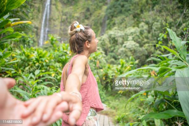 follow me to concept- young woman leading boyfriend to tropical rainforest and waterfalls - water fall hawaii stock pictures, royalty-free photos & images