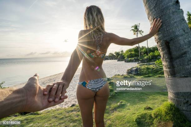 follow me to concept young woman leading boyfriend to tropical beach at sunset - cebu stock photos and pictures