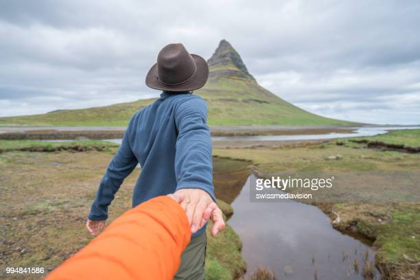 follow me to nature, man leading girlfriend to kirkjufell mountain - following stock pictures, royalty-free photos & images