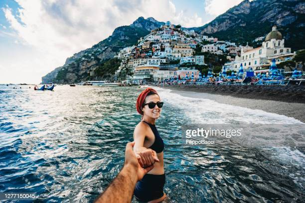 follow me to positano, italy - a young beautiful woman is leading her partner to the small town of positano - naples italy stock pictures, royalty-free photos & images