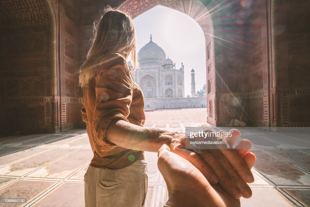 Follow me to the Taj Mahal, India. Female tourist leading boyfriend to there magnificent famous Mausoleum in Agra. People travel concept : Stock Photo