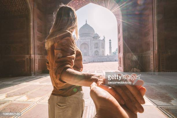 follow me to the taj mahal, india. female tourist leading boyfriend to there magnificent famous mausoleum in agra. people travel concept - turista foto e immagini stock