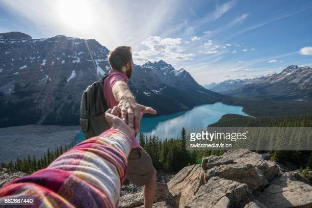 Suivez-moi à - fille plus jeune homme au sommet de la montagne