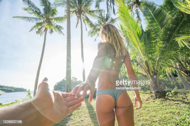 follow me to, young woman leading boyfriend to palm tree forest - following moving activity stock pictures, royalty-free photos & images