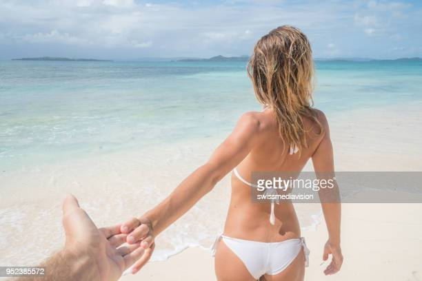 follow me to, young woman leading boyfriend to tropical paradise beach - following stock pictures, royalty-free photos & images