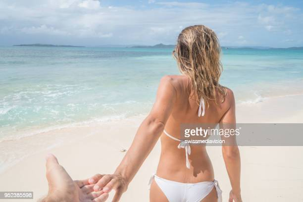 follow me to, young woman leading boyfriend to tropical paradise beach - following moving activity stock pictures, royalty-free photos & images